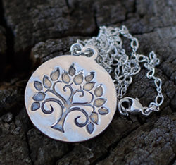 """This beautiful tree of life silver necklace has a statement medallionas a charm that has been made by hand to create its organic look.The tree of life represents as mentioned in the books of Genesis and Revelation, is a life-giving tree created to enhance and perpetually sustain the physical life of humanityThe sterling silver tree of life necklace will be a beautiful present for someone special that will keep it close to her heart. The necklace is made of fine silver and has a hand stamped charm bar that is mounted on an elegant silver chain. The silver bar charm measures approximately 7/8"""" diameter"""